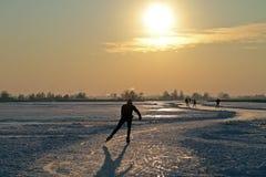 Patinaje de hielo los Países Bajos en la puesta del sol Imagen de archivo libre de regalías