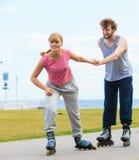 Patinaje de los pares del patinador del rodillo al aire libre Imagen de archivo libre de regalías