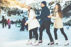 Patinaje divertido al aire libre, pista de las muchachas y del muchacho de los adolescentes de hielo Fotos de archivo libres de regalías