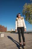 Patinaje sobre ruedas alegre de la muchacha en el parque y feliz sonrisa Imágenes de archivo libres de regalías