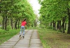Patinaje sobre ruedas atlético del adolescente en un parque Imagen de archivo libre de regalías