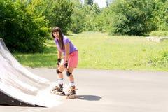 Patinaje sobre ruedas de la chica joven en una rampa Foto de archivo libre de regalías