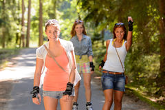 Patinaje sobre ruedas de tres amigos de las mujeres al aire libre Foto de archivo libre de regalías