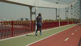 Patinaje sobre ruedas femenino positivo con vuelta al aire libre metrajes