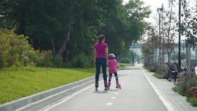 Patinaje sobre ruedas joven de la madre con su hija metrajes