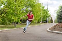 Patinaje sobre ruedas joven del adolescente alrededor de una curva Foto de archivo