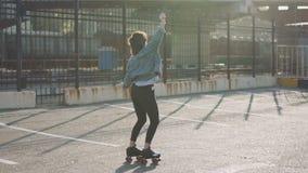 Patinaje sobre ruedas y baile hermosos atractivos del montar a caballo de la mujer joven en las calles Fondo urbano, cámara lenta almacen de video