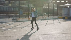 Patinaje sobre ruedas y baile hermosos atractivos del montar a caballo de la mujer joven en las calles Fondo urbano, cámara lenta metrajes