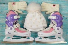 Patines de hielo de los niños con de medida adaptable y accesorios en el piso de madera Foto de archivo