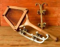 Patines de hielo del vintage y estafa de tenis en fondo de madera Patines de hielo y raket retros del tenis Imágenes de archivo libres de regalías