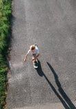 Patines del muchacho en el monopatín en la carretera de asfalto Fotos de archivo libres de regalías