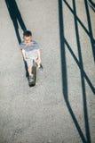 Patines del muchacho en el monopatín en la carretera de asfalto Fotos de archivo