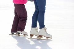 Patines del niño y del adulto en la pista de hielo Imágenes de archivo libres de regalías