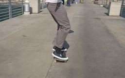 Patines del patinador del muchacho en el embarcadero imagen de archivo