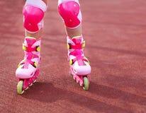 Patines en línea de los Rollerblades de un primer del niño en la acción al aire libre Imagen de archivo libre de regalías