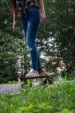 Patines hermosos de la chica joven en el monopatín en parque Imagen de archivo