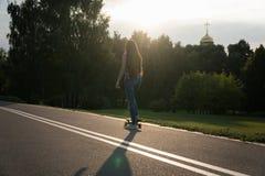 Patines hermosos de la chica joven en el monopatín en la puesta del sol Imagen de archivo