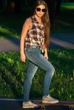 Patines hermosos de la chica joven en el monopatín en la puesta del sol Imagenes de archivo