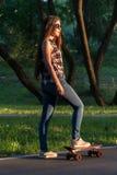 Patines hermosos de la chica joven en el monopatín en la puesta del sol Fotografía de archivo