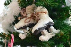 Patines hermosos de la decoración en un árbol de navidad verde Imágenes de archivo libres de regalías