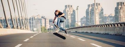 Patineur faisant des tours et sautant sur le pont en route de rue PA photo stock