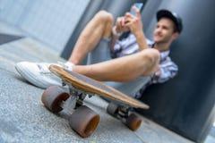 Patineur masculin heureux amusant avec le smartphone Photographie stock libre de droits