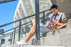 Patineur masculin insouciant à l'aide du téléphone portable Image libre de droits