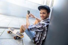 Patineur masculin joyeux amusant avec le smartphone Photos libres de droits