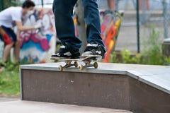 Patineur rectifiant 50 50 sur le mur en parc de patin avec le painte de graffiti Image stock