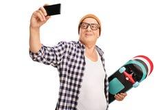 Patineur supérieur prenant un selfie avec son téléphone Image stock