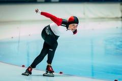 Patineurs de vitesse de jeune fille sur une piste de patinage courante de voie Photographie stock libre de droits
