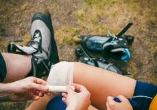 Patineuse de femme avec le genou blessé de jambe Photographie stock
