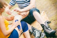 Patineuse de femme avec le genou blessé de jambe Photographie stock libre de droits