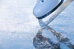 Patins de femme freinant la glace, frazil Photographie stock libre de droits