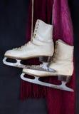 Patins de gelo brancos que penduram com o lenço vermelho e cor-de-rosa de lãs Imagem de Stock