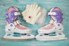 Patins de gelo das crianças com de medida ajustável e acessórios no assoalho de madeira imagem de stock