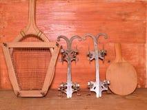Patins de gelo do vintage, raquete de tênis e raquete de tênis de mesa no fundo de madeira Raket retro do tênis dos patins de gel Imagens de Stock Royalty Free