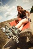 Patins de rolo da equitação da jovem mulher Fotografia de Stock