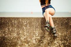 Patins de rolo vestindo da jovem mulher feliz imagem de stock