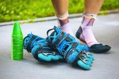 Patins de rouleau bleus avec des cônes de slalom et chaussettes de rouleau sur le mâle le Image libre de droits