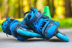 Patins de rouleau bleus avec des cônes de slalom se trouvant sur l'asphalte Image libre de droits