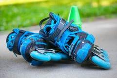 Patins de rouleau bleus avec des cônes de slalom se trouvant sur l'asphalte Photographie stock libre de droits