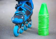 Patins de rouleau bleus avec des cônes de slalom se trouvant sur l'asphalte Photo libre de droits