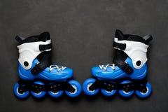Patins de rouleau bleus sur le fond foncé de panneau de craie Photographie stock libre de droits
