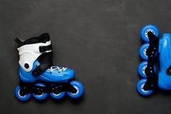 Patins de rouleau bleus sur le fond foncé de panneau de craie Images stock