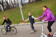 Patins de rouleau heureux de tour d'amie scooter et bicyclette sur le remorquage Photographie stock