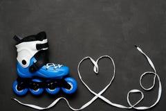 Patins et coeur de rouleau bleus des dentelles sur le fond foncé de panneau de craie Photo stock