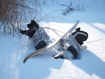 Patins et un bâton de hockey sur le lac Photos stock