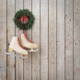 Patins que penduram na parede de madeira das pranchas com festão, fundo do Natal do inverno Imagem de Stock Royalty Free
