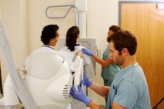 Patiënt in röntgenstraal met arts en 2 technici Royalty-vrije Stock Afbeeldingen